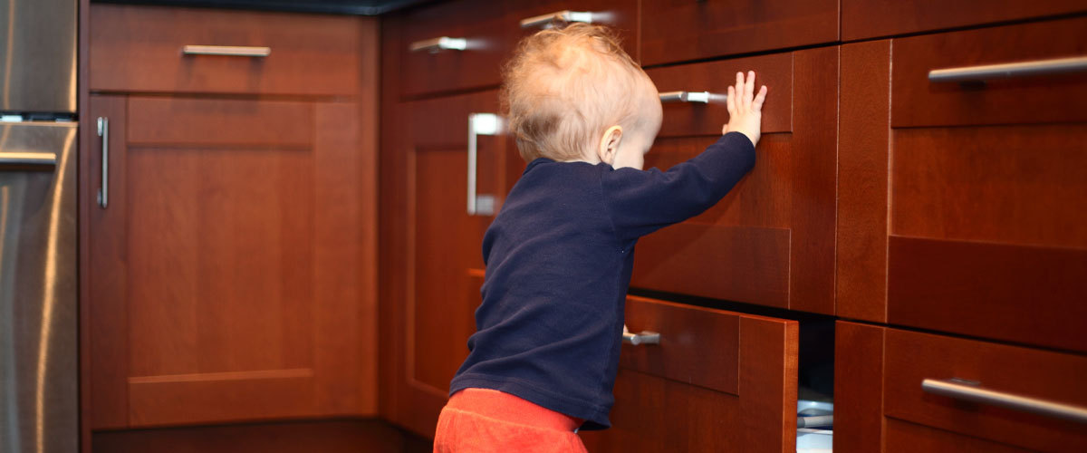 Standing baby opening a drawer in the kitchen.