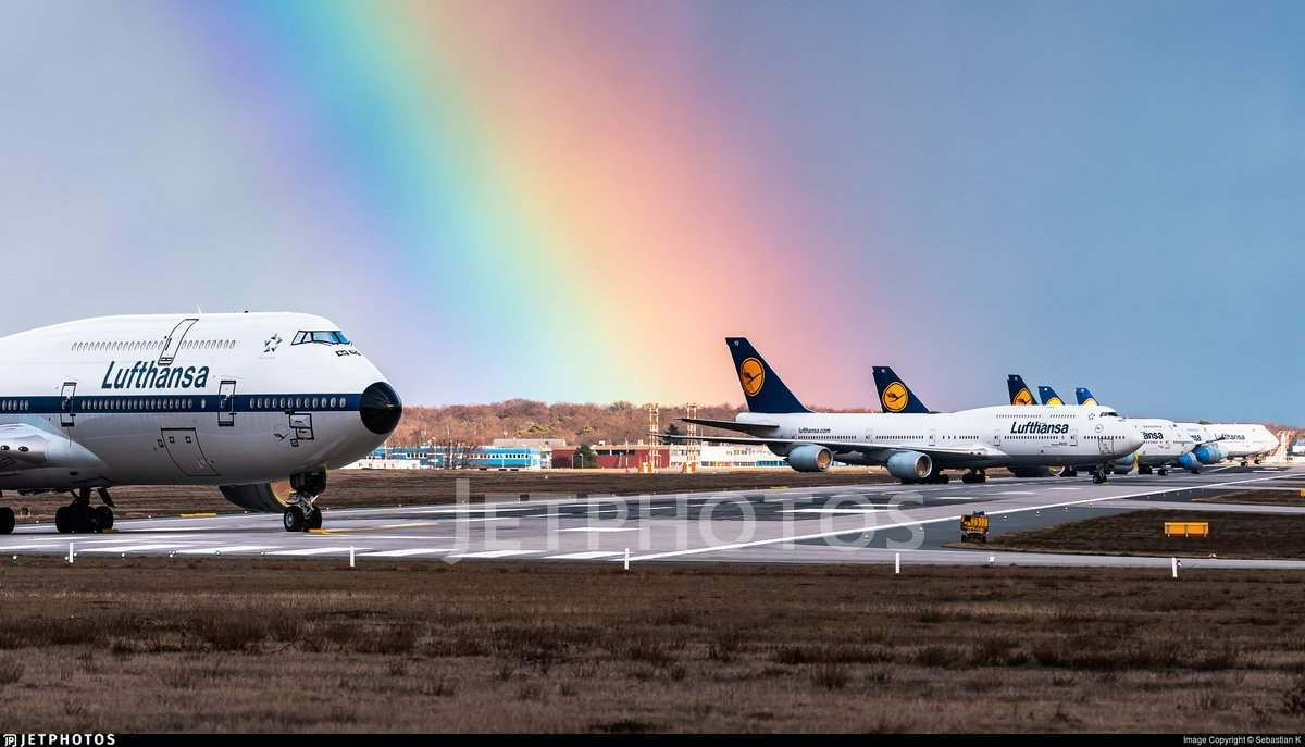 A rainbow ends at the runway in Frankfurt with Lufthansa 747s in storage