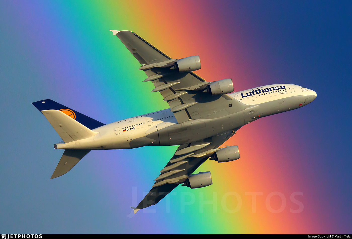 A Lufthansa A380 passing in front of a rainbow