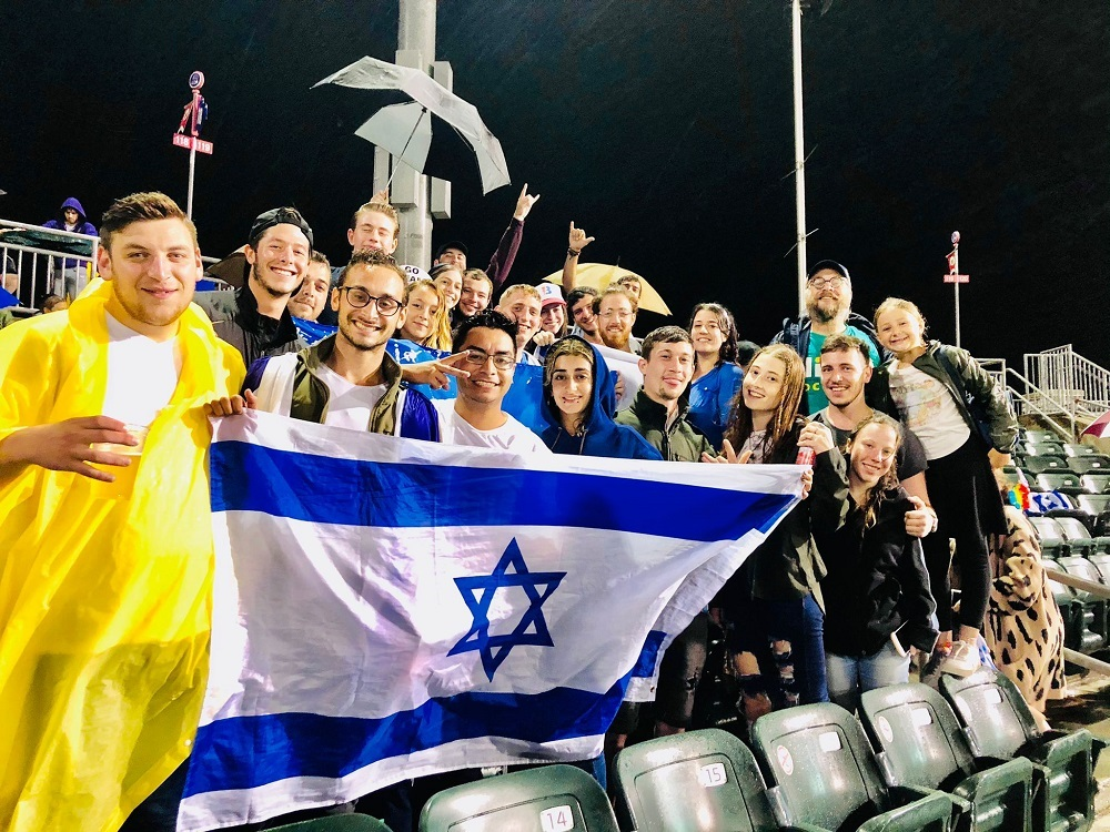 group holding Israeli flag at Boulders game