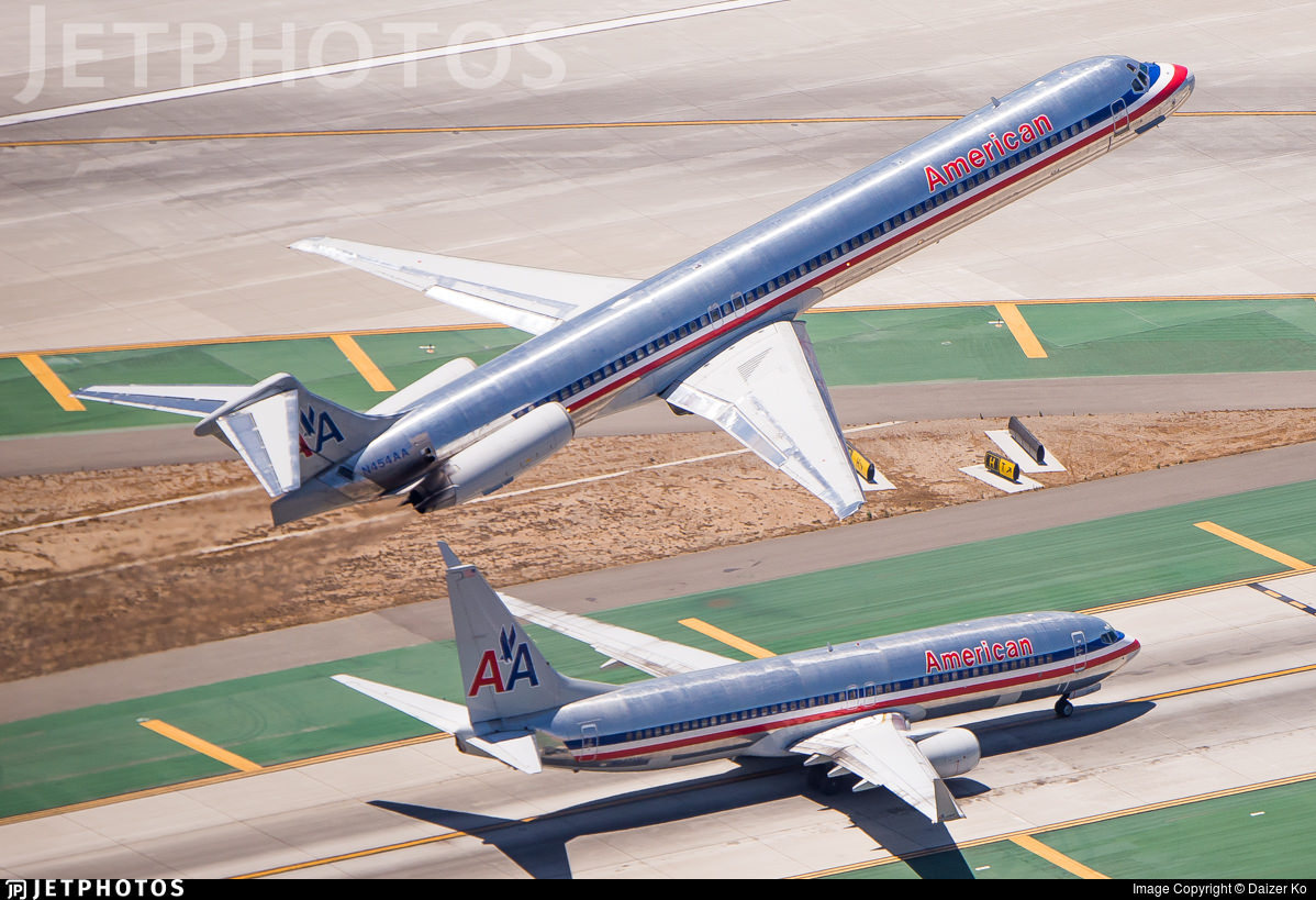 An American Airlines MD-82 departing Los Angeles while a 737 taxies below. Both in bare metal livery.