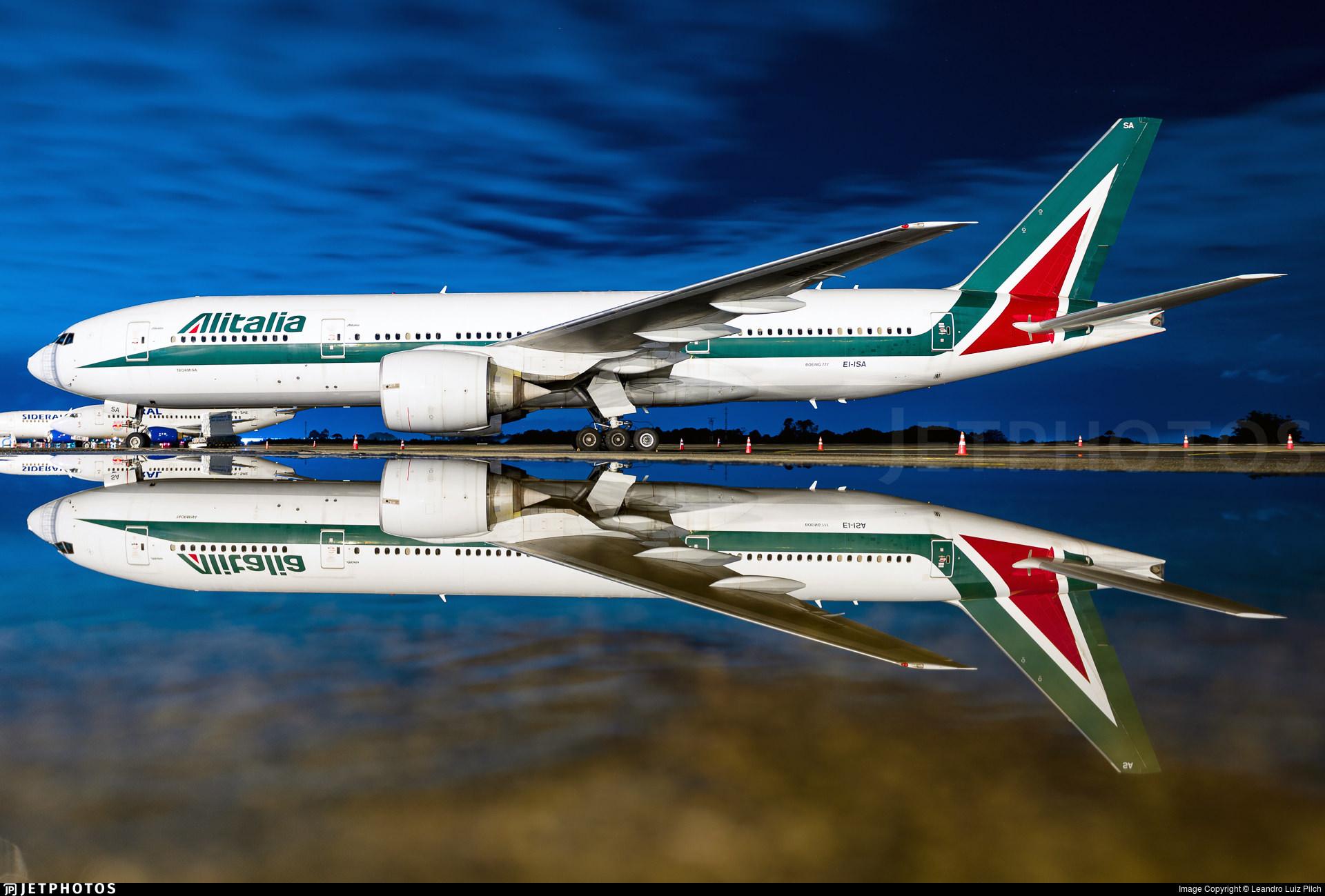 An Alitalia 777 reflecting on wet pavement in Curitiba