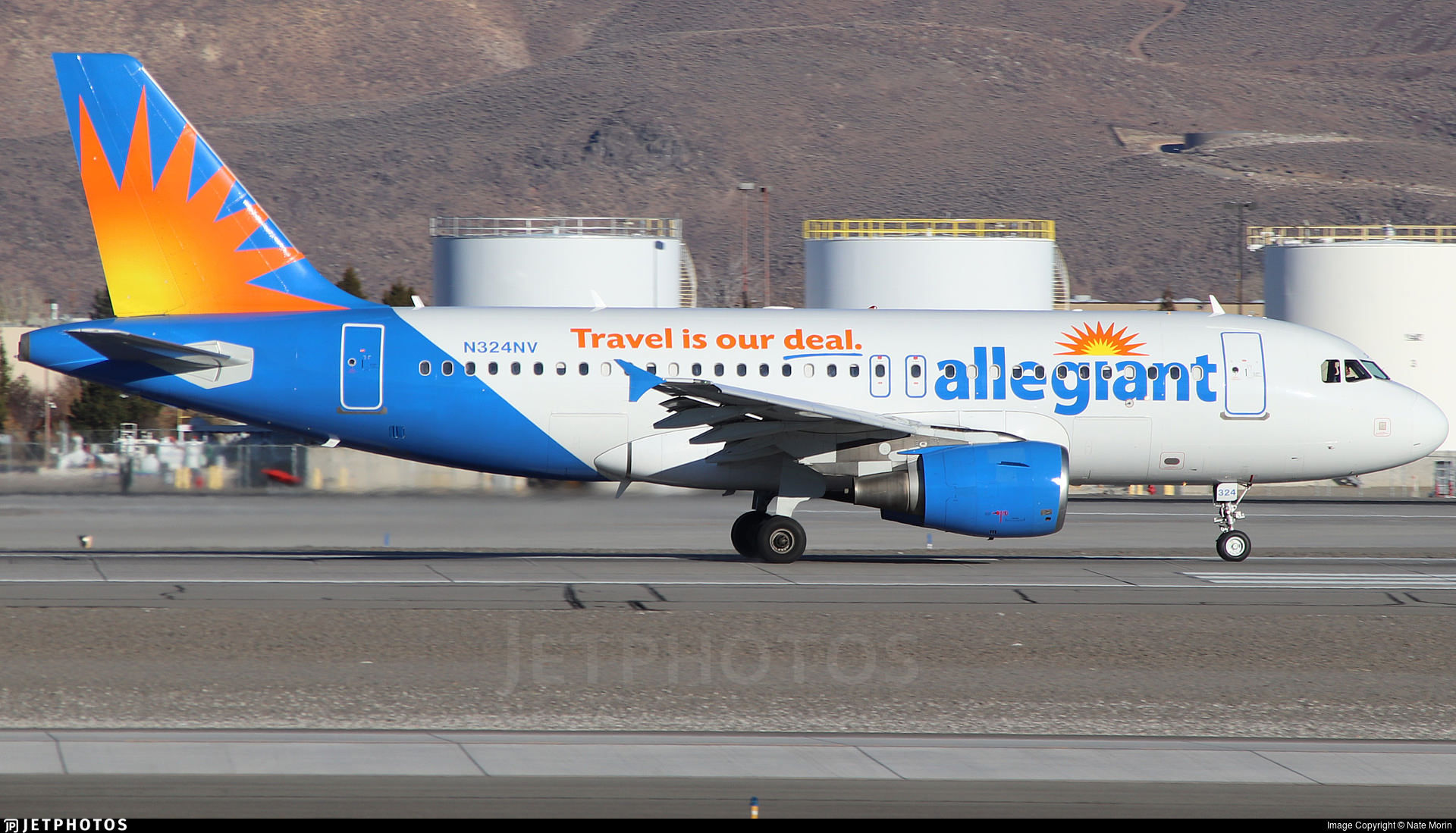 An Allegiant A319 in front of the fuel tanks at Reno Airport