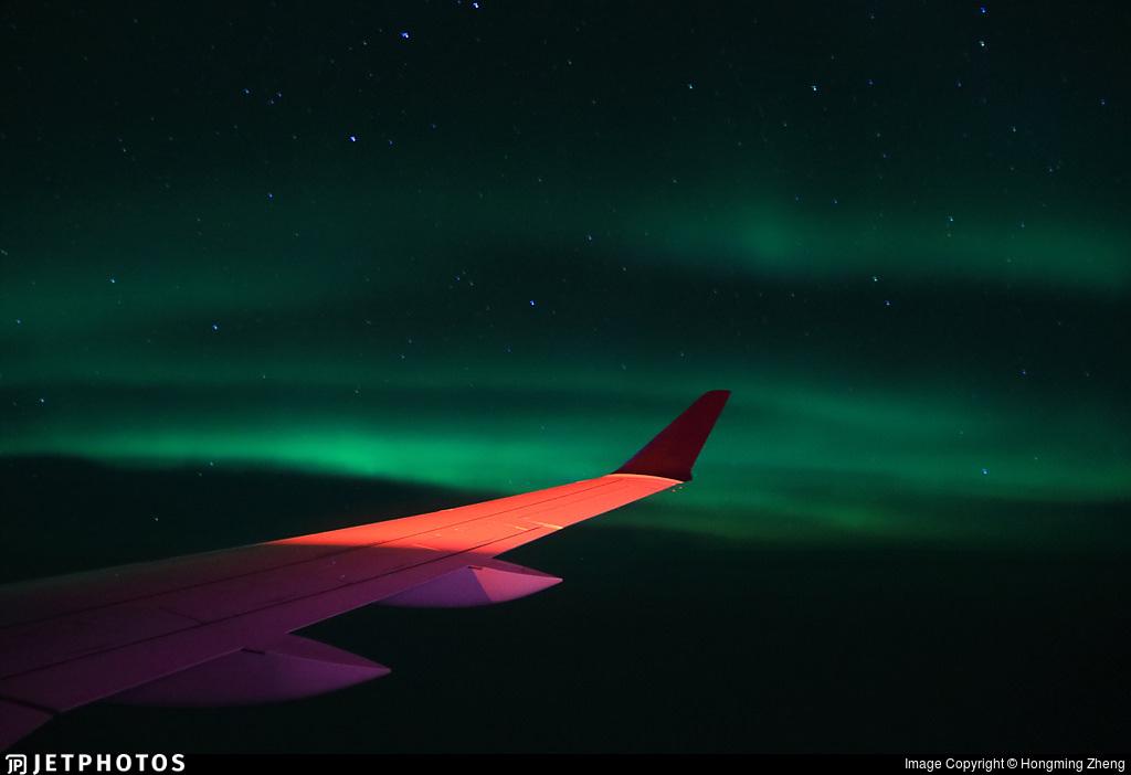 Northern Lights outside a Delta A220 over Alaska