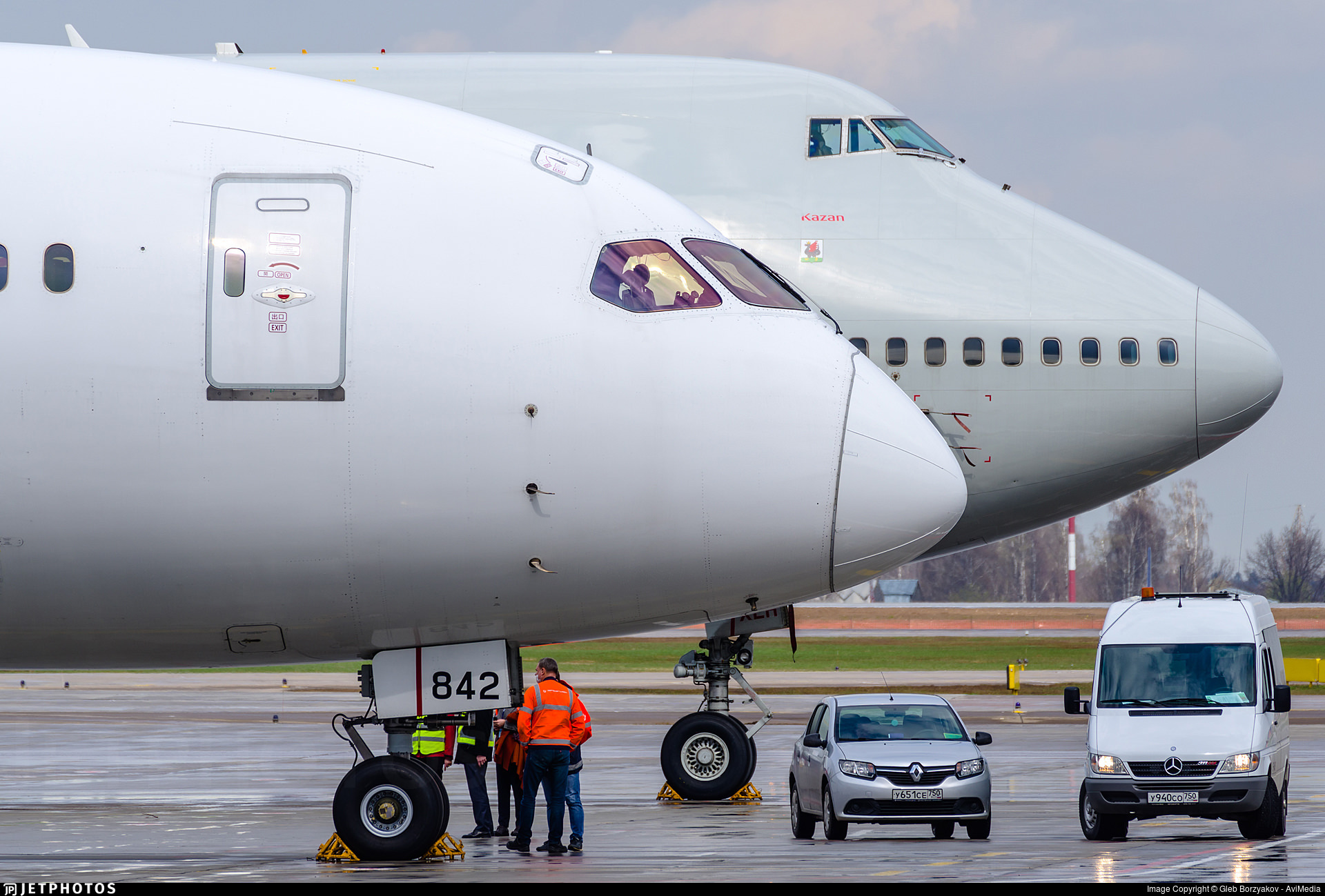 A 787 and 747 parked next to each other in Moscow with just the nose of each aircraft visible