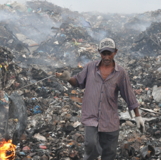 an image of a man standing in front of a huge landfill of trash and plastic waste