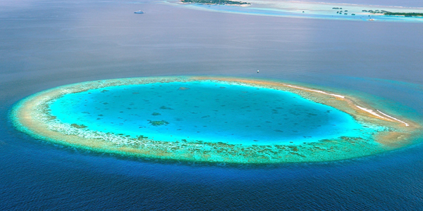 Aerial photo shows a coral atoll in the Maldives. A depression is visible in the middle of the coral ring.