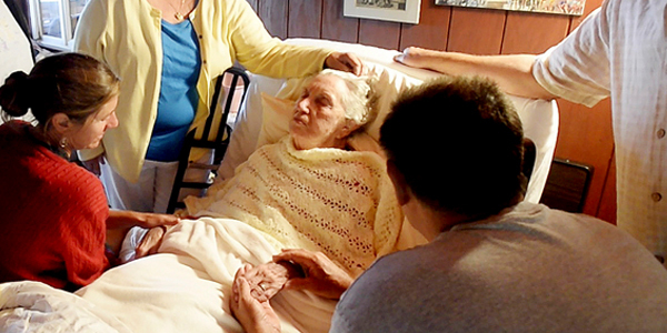 Photograph of an elderly woman lying in bed. Standing and sitting around her are family members, two of them holding her hands. A hospice aide and a bottle of lotion are seen at the foot of the bed.