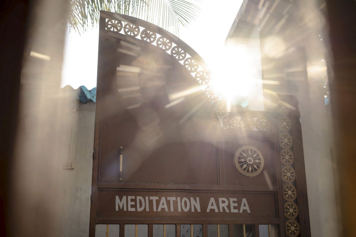 Rays of sunlight shining through the gate of a Vipassana Meditation Center.