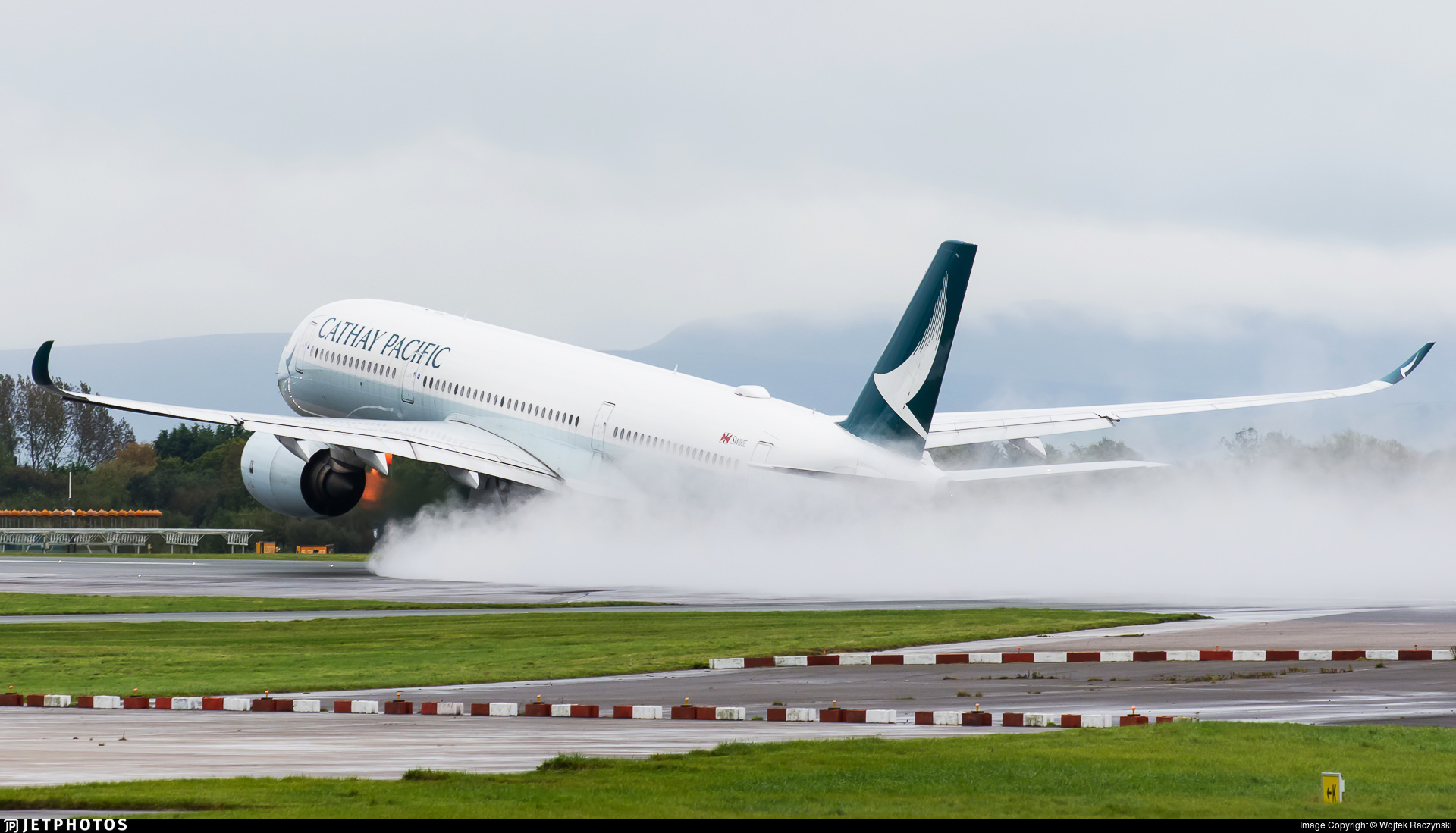 A Cathay Pacific A350 lifting off from a wet Manchester