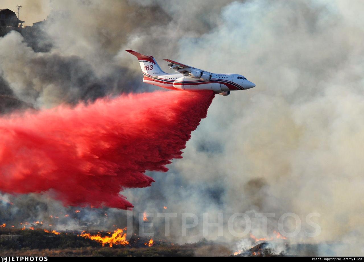 An AeroFlite RJ85 dropping fire retardant on a fire