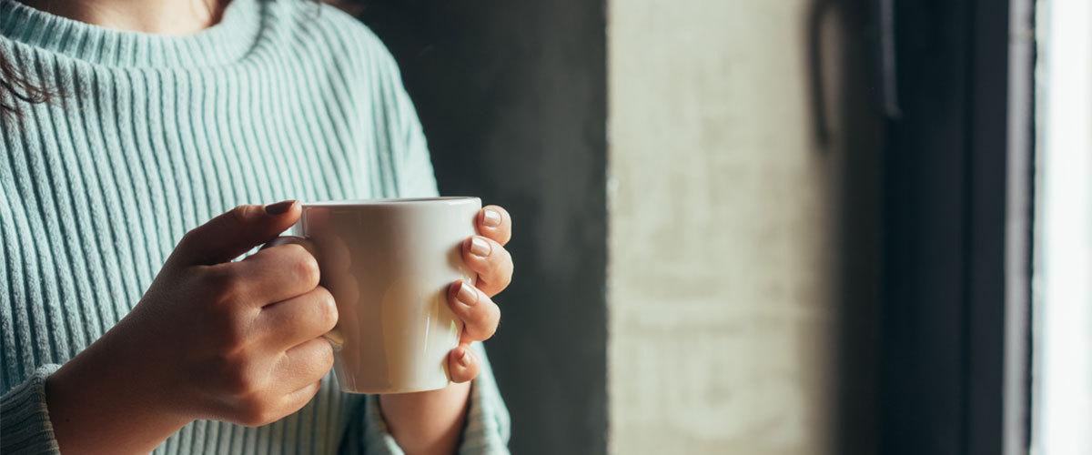 Adult holding mug.