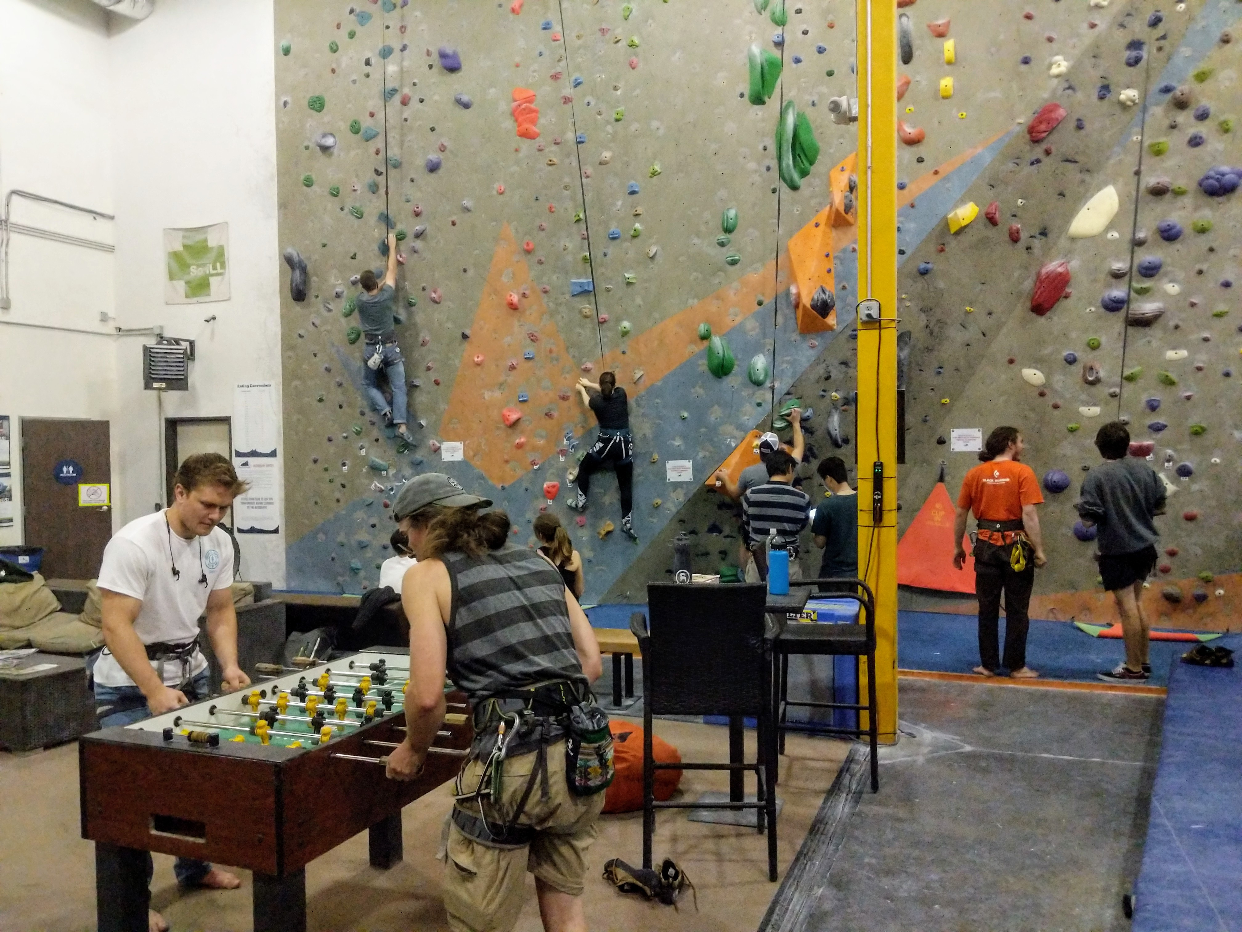 Wide shot of the gym with climber climbing and people playing foosball