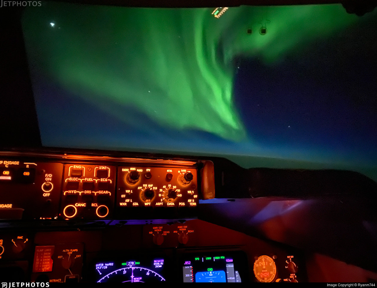 The Northern Lights shine outside the flight deck of a National Airlines 747