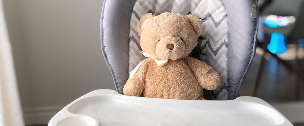Teddy bear sitting in high chair.