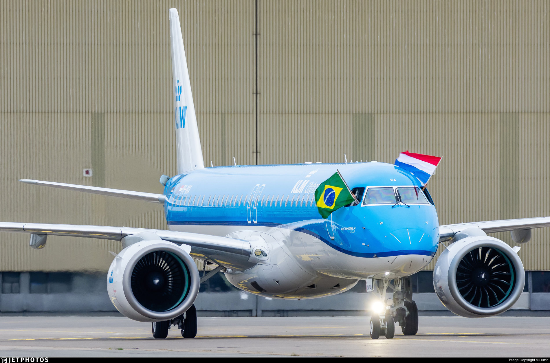 KLM's first Embraer E195-E2 arriving in Amsterdam on delivery with the captain waving a Dutch flag out the window and the First Officer waving a Brazilian flag  out their window. Embraer is a Brazilian company.