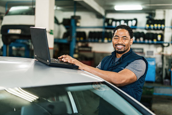 Man smiling and looking at the camera, while working on a laptop in a garage.