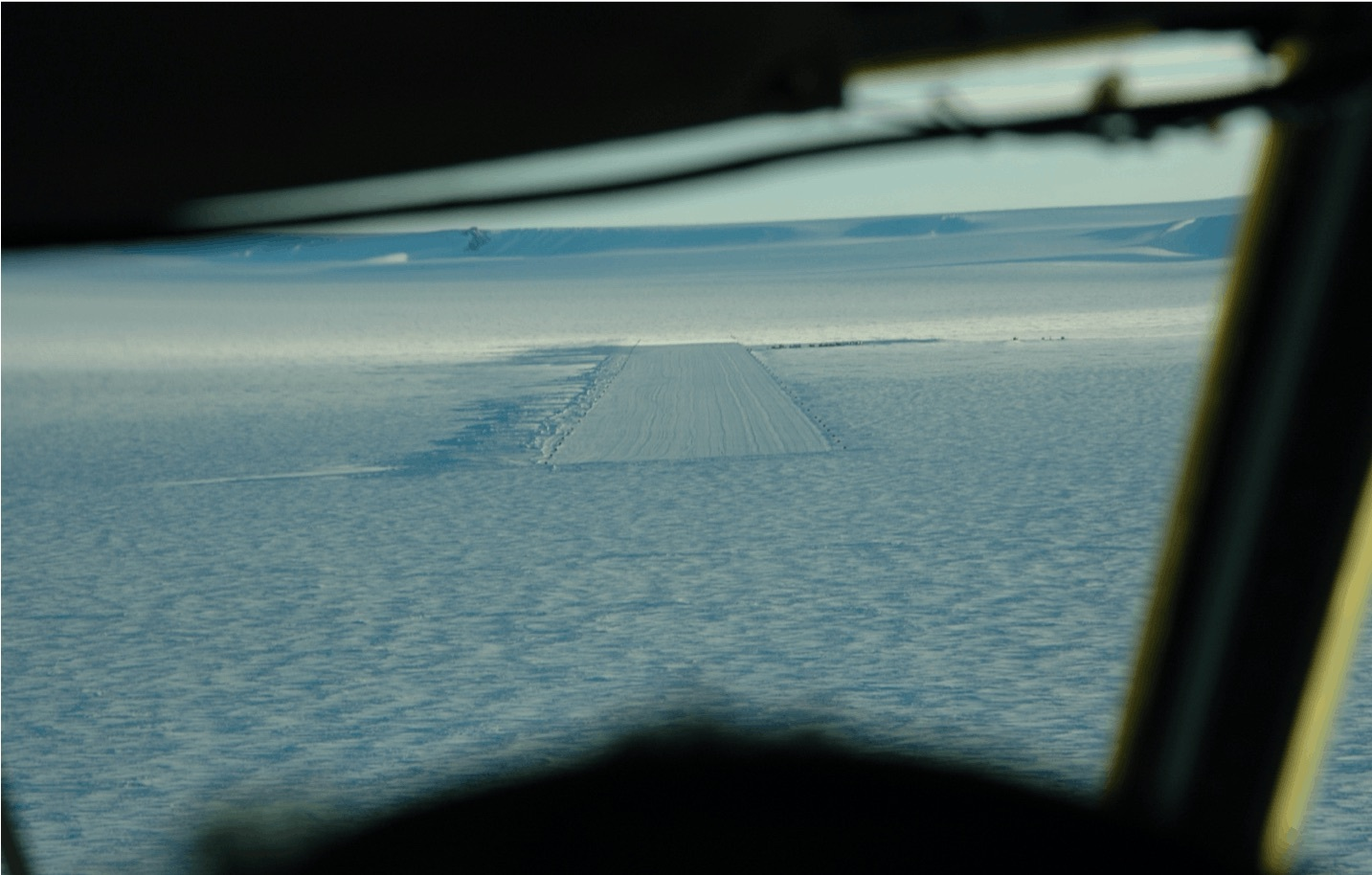 Looking out at the Troll Airfield from the flight deck of an aircraft on approach to the runway.