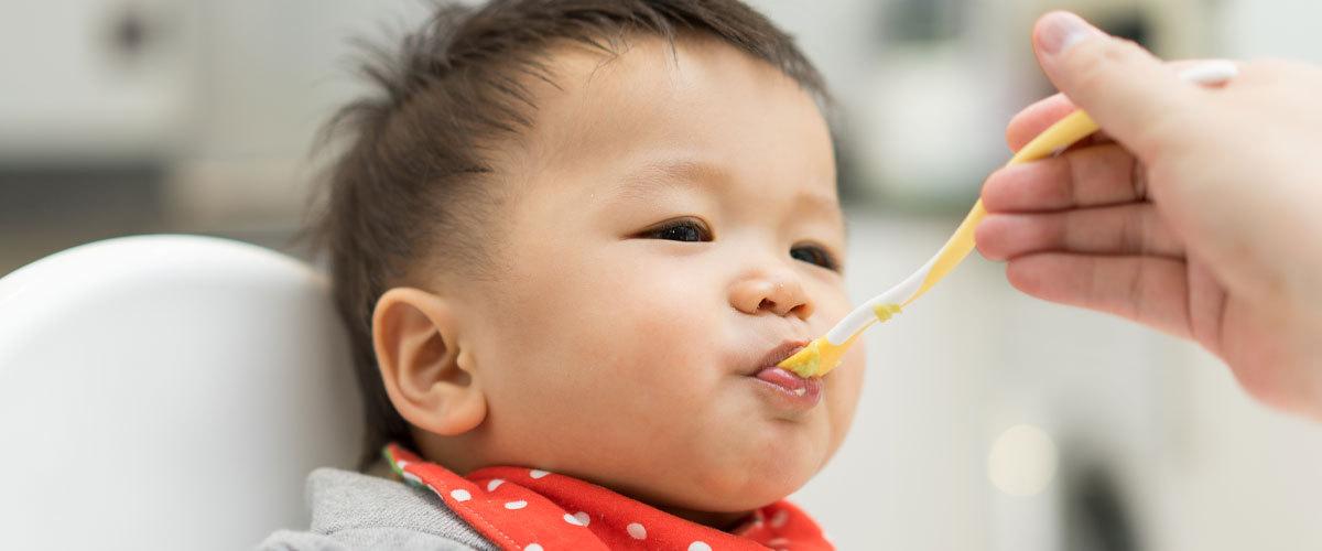 Adult spoon feeding a baby.